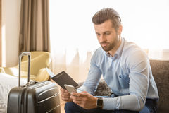Young man business traveler hotel room accomodation. Young male business traveler hotel accomodation using smartphone stock photography