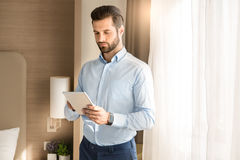 Young man business traveler hotel room accomodation. Young male business traveler hotel accomodation using tablet stock photo