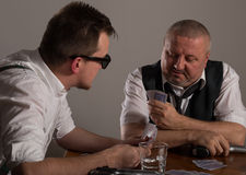 Young man and businessman playing poker with guns Royalty Free Stock Images