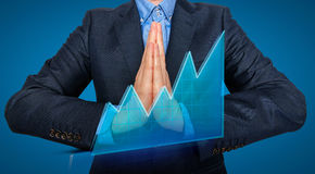 Young Man Businessman praying and Wishing Hard. Blue backgroundk - Stock Image Royalty Free Stock Photos
