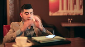 Young man businessman tired from work. In cafe stock video