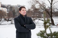 Young man, businessman walking in winter park. Young man, businessman walking alone in winter park. A smiling middle-aged man in a black coat walks around the Stock Image