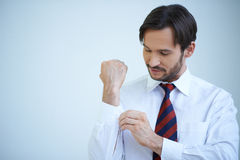 Young man buttoning his cuffs. On his shirt as he gets dressed ready for a day at the office Stock Photo