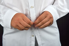 Young man buttoning his white shirt on a dark background. He is Royalty Free Stock Images