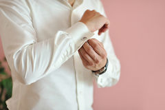 Young man buttoning shirt Stock Images