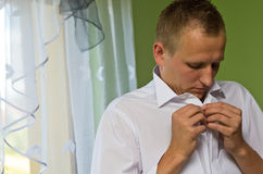 Young Man Buttoning White Shirt Royalty Free Stock Photo