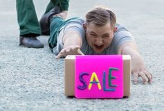A young man buyer is lying on the sidewalk at the store and screaming with tension crawling to the box with the inscription sale. A young man buyer is lying on royalty free stock image
