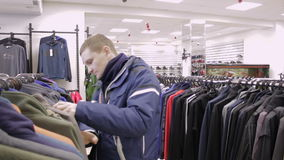 Young man is buying clothes at the store. Warm sportswear stock video