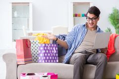 The young man buying clothing online and running blog Royalty Free Stock Image