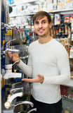 Young man buying new water cock in supermarket Royalty Free Stock Images