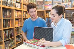 Young man buying poker chip in game store Royalty Free Stock Photo