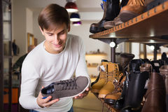 Young man buying summer shoes. In a shoe shop royalty free stock image