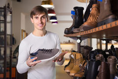Young man buying summer shoes Royalty Free Stock Photography