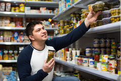 Young man buying tinned food Stock Photo