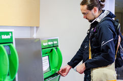 Young man buying train ticket. From machine Stock Image