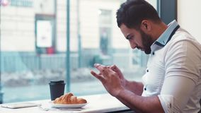 Young man in a café, taking several photos of his breakfast coffee and croissants to post it online. Modern lifestyle stock video footage