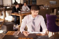 Young man at cafe table reading newspaper. Royalty Free Stock Photo