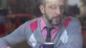 A young man in a cafe tells another man about a creative project stock video