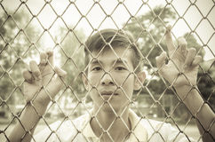 Young man caged behind metal or steel net Stock Images