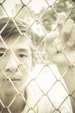 young man caged behind metal or steel net Royalty Free Stock Images