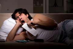 The young man calculating expences night at home. Young man calculating expences night at home royalty free stock photo