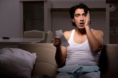 The young man calculating expences night at home. Young man calculating expences night at home royalty free stock image