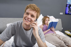 Young Man On Call In Bedroom Stock Photos