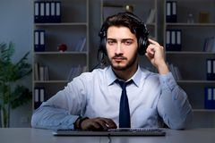 Young man in call center concept working late overtime in office Royalty Free Stock Photos