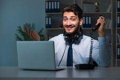 Young man in call center concept working late overtime in office Stock Photography