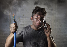 Young man calling for help after accident with dirty burnt face in funny sad expression. Young man holding electrical cable smoking after electrical accident and Royalty Free Stock Photos