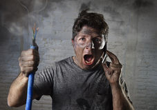 Young man calling for help after accident with dirty burnt face in funny sad expression Royalty Free Stock Photos