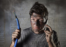 Young man calling for help after accident with dirty burnt face in funny sad expression. Young man holding electrical cable smoking after electrical accident and Royalty Free Stock Image