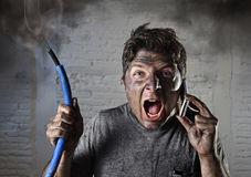 Young man calling for help after accident with dirty burnt face in funny sad expression Royalty Free Stock Photography