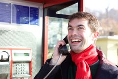 Young man calling from phone booth Royalty Free Stock Photos