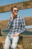 Young man calling by phone in the countryside. Royalty Free Stock Images
