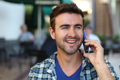 Young man calling by phone outside.  Royalty Free Stock Image