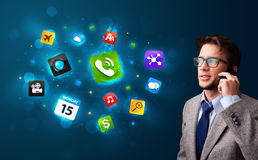 Young man calling by phone with various icons Stock Images