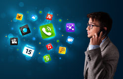 Young man calling by phone with various icons Stock Image