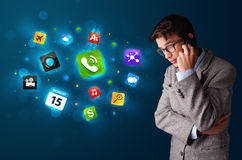 Young man calling by phone with various icons Royalty Free Stock Images