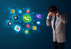 Young man calling by phone with various icons Stock Photos