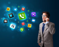 Young man calling by phone with various icons Royalty Free Stock Photos