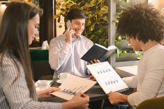 Young man calling to clients, his colleagues studying financial statistics. Informal team meeting in cafe. Young men calling to clients, his colleagues studying stock photography