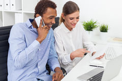 Young man callling while his colleague shows him something Royalty Free Stock Photo
