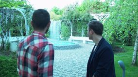 A young man came to visit a friend in a spa. Two friends are talking at the fountain in the park of the treatment center. Friends are forgiven. Two brothers stock video