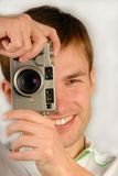 Young man with  camera. In hands is going to photograph, close up Royalty Free Stock Image