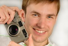 Young man with  camera. In  hand specifies  finger, close up Royalty Free Stock Photos