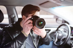 Young man with a camera in the car. The man in the car reviews the photos on the camera. Spy, paparazzi, journalist, photographer Stock Photography
