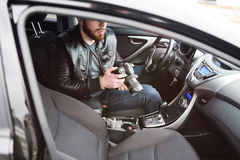 Young man with a camera in the car. The man in the car reviews the photos on the camera. Spy, paparazzi, journalist, photographer Royalty Free Stock Photography