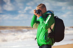 Young man with camera makes sea snapshot Stock Photo