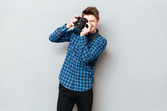Young man with camera making photo. Over grey royalty free stock image